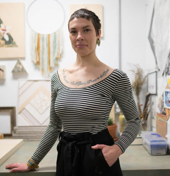 A portrait of artist Caitlin Bodewitz standing in her studio, wearing a striped shirt and black pants, with close cropped black hair.
