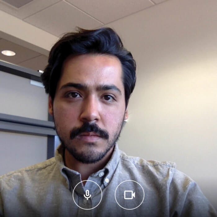 A portrait of artist Sergio Serrano, which is a screenshot from a video calling app. Sergio wears a light grey shirt, with black hair and a beard and moustache, and is in a white walled room.