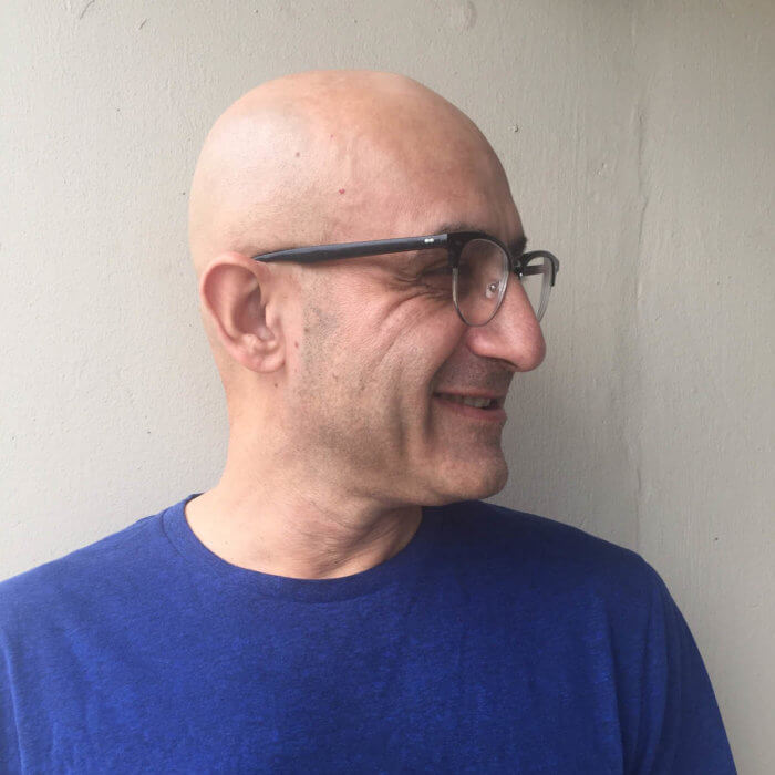 A portrait of artist Riaz Mehmood, looking to the right and smiling. Riaz has a shaved head and wears glasses and a blue shirt.