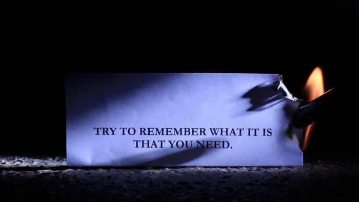 """a screengrab of a blue lit paper with shadows across it and a flame in a corner, with the words """"Try to remember what it is that you need."""""""