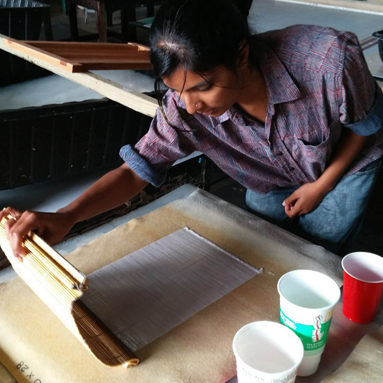 photo of Radha Pandey leaning over a desk while handling handmade paper
