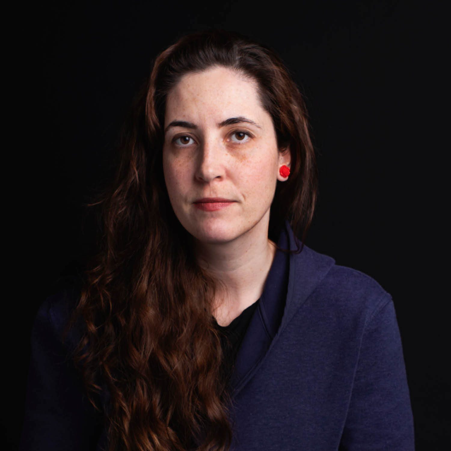 Portrait of Tiffany Shaw-Collinge looking at the camera, wearing a dark blue top and long dark brown hair